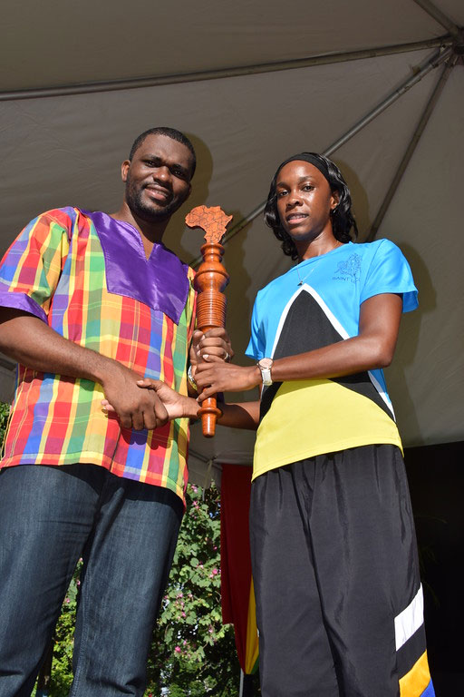 Olympic High-jumper Levern Spencer (in Olympic national flag gear) handed the CARICOM Reparations Baton to Dean of the CARICOM Youth Ambassadors Charde Desir, during the Reparations and Kwéyol Youth Rally held after the October 29 CARICOM Reparations Baton Relay.